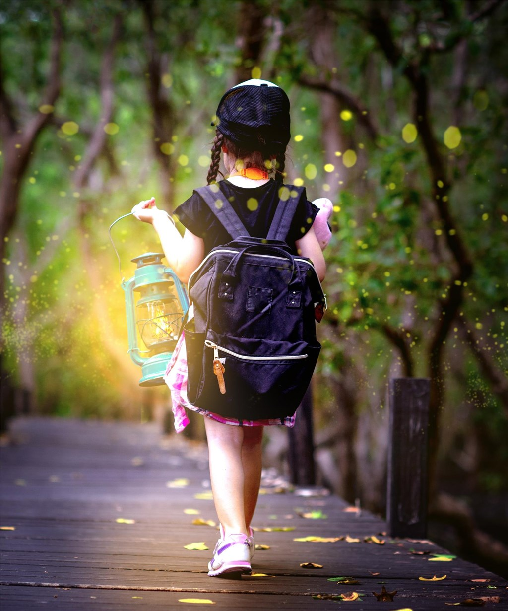 Child with backpack and lantern walking through forest and fireflies
