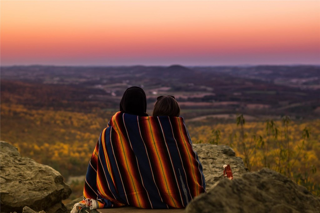 A couple wrapped in a blanket enjoy the sunset over the vista from South Lookout